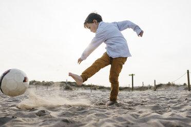Little boy playing soccer on the beach kicking the ball - JRFF03238