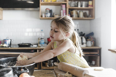 Little girl rolling out dough in the kitchen - KMKF00907
