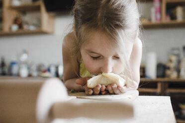 Little girl smelling freshly prepared stuffed pastry - KMKF00910