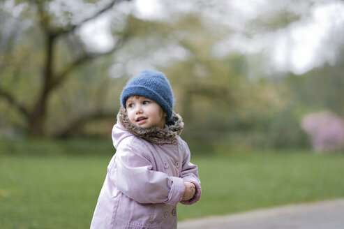 Portrait of little girl in a park wearing blue hat and pink coat - EYAF00188