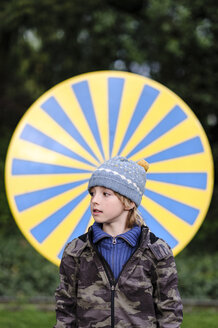 Portrait of boy wearing warm clothing standing in front of yellow and blue circle - EYAF00194