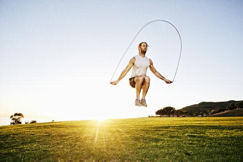 Caucasian man jumping rope in sunny field - BLEF02111
