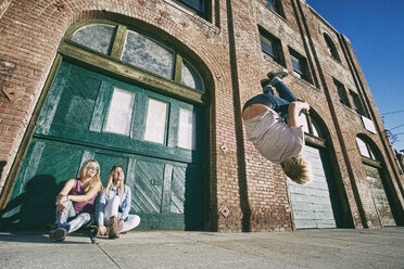 Woman watching man skateboarding on urban sidewalk - BLEF02126