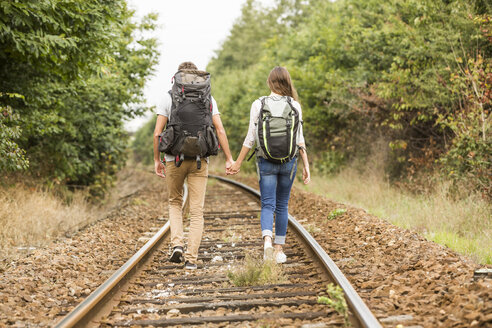 Caucasian couple walking on train tracks - BLEF02180