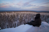 Caucasian man sitting in snow admiring scenic view of forest - BLEF02216