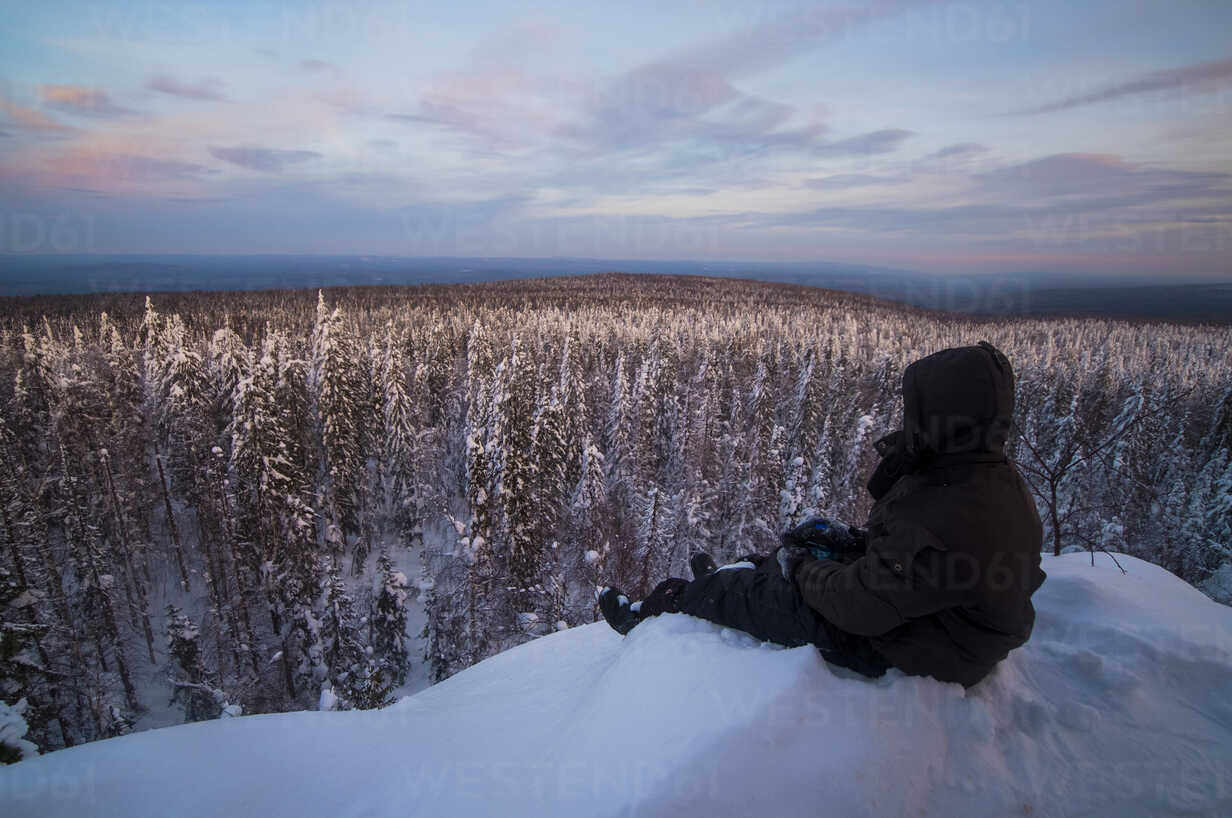Caucasian man sitting in snow admiring scenic view of forest - BLEF02216 - Aleksander Rubtsov/Westend61