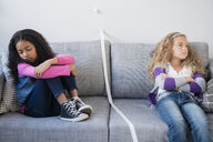 Frustrated girls dividing sofa with tape - BLEF02298