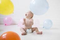 Caucasian baby boy sitting on floor watching balloons - BLEF02352