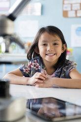 Smiling Asian girl leaning posing at desk - BLEF02382