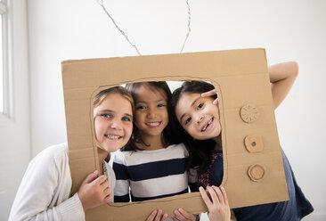 Portrait of smiling girls holding cardboard television - BLEF02391
