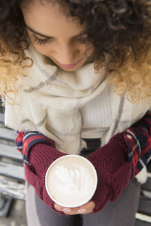 Mixed Race woman holding coffee cup with leaf in foam - BLEF02400