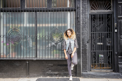 Mixed Race woman leaning on gated window in city - BLEF02412