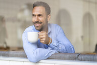Smiling businessman with cup of coffee looking out of window - DIGF06943