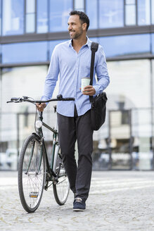 Businessman with bicycle on the go in the city - DIGF06964