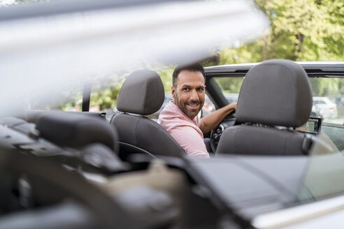 Man sitting in car with closing convertible top - DIGF06988