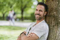 Portrait of smiling man leaning against a tree in park - DIGF07003