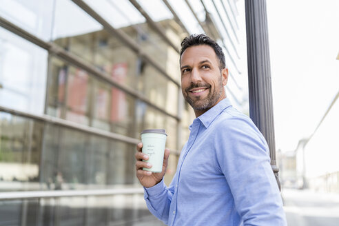 Portrait of smiling businessman with takeaway coffee in the city - DIGF07006