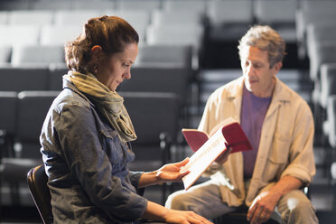 Caucasian actors rehearsing with scripts in theater - BLEF02537