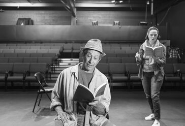 Caucasian actors rehearsing with scripts in theater - BLEF02543