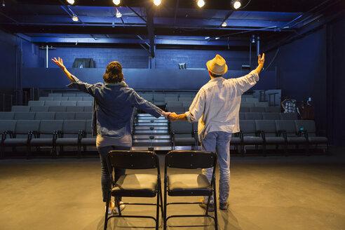 Caucasian actors rehearsing waving in theater - BLEF02546