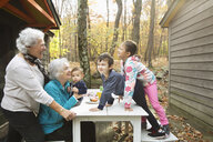 Grandmothers playing with grandchildren at breakfast table outdoors - BLEF02702