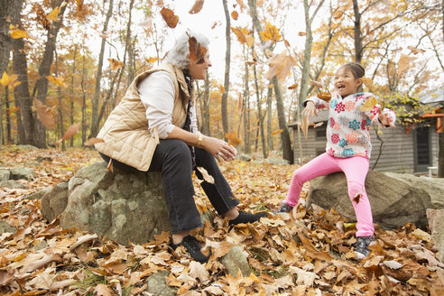 Grandmother and granddaughter playing with autumn leaves - BLEF02708