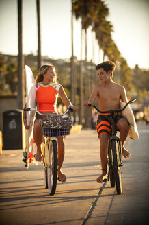 Teenage boy and girl riding bicycles carrying surfboards - BLEF02744