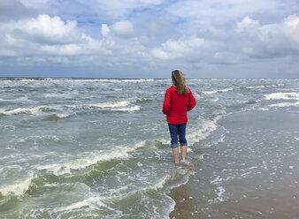 Belgium, Flanders, North Sea, woman standing barefoot in ocean waves, relaxing - GWF06071