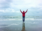 Belgium, Flanders, North Sea, woman standing on beach, relaxing, enjoying freedom and the sea - GWF06074