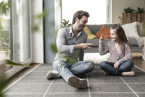 Young man and little girl sitting at home, playing paper scissors stone - UUF17312