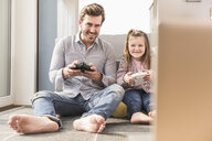 Young man and little girl playing computer game with gaming console - UUF17333