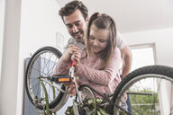 Young man and little girl repairing bicycle together - UUF17366