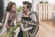 Young man and little girl repairing bicycle together - UUF17369