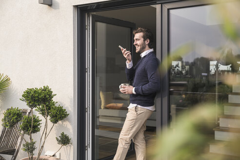Young man leaning in door of his house, holding cup of coffee, using smartphone - UUF17375