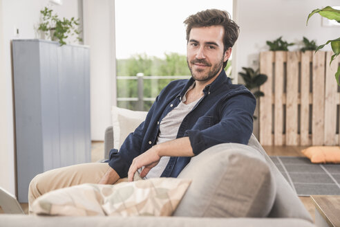 Young man sitting on couch at home, smiling - UUF17405