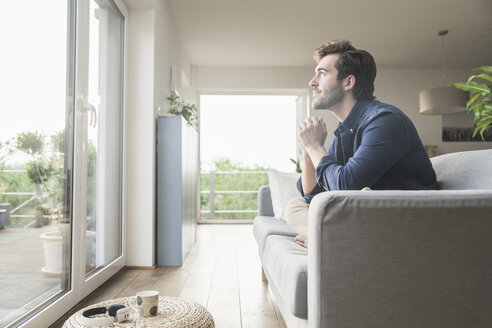 Young man sitting on couch at home, looking out of window - UUF17408