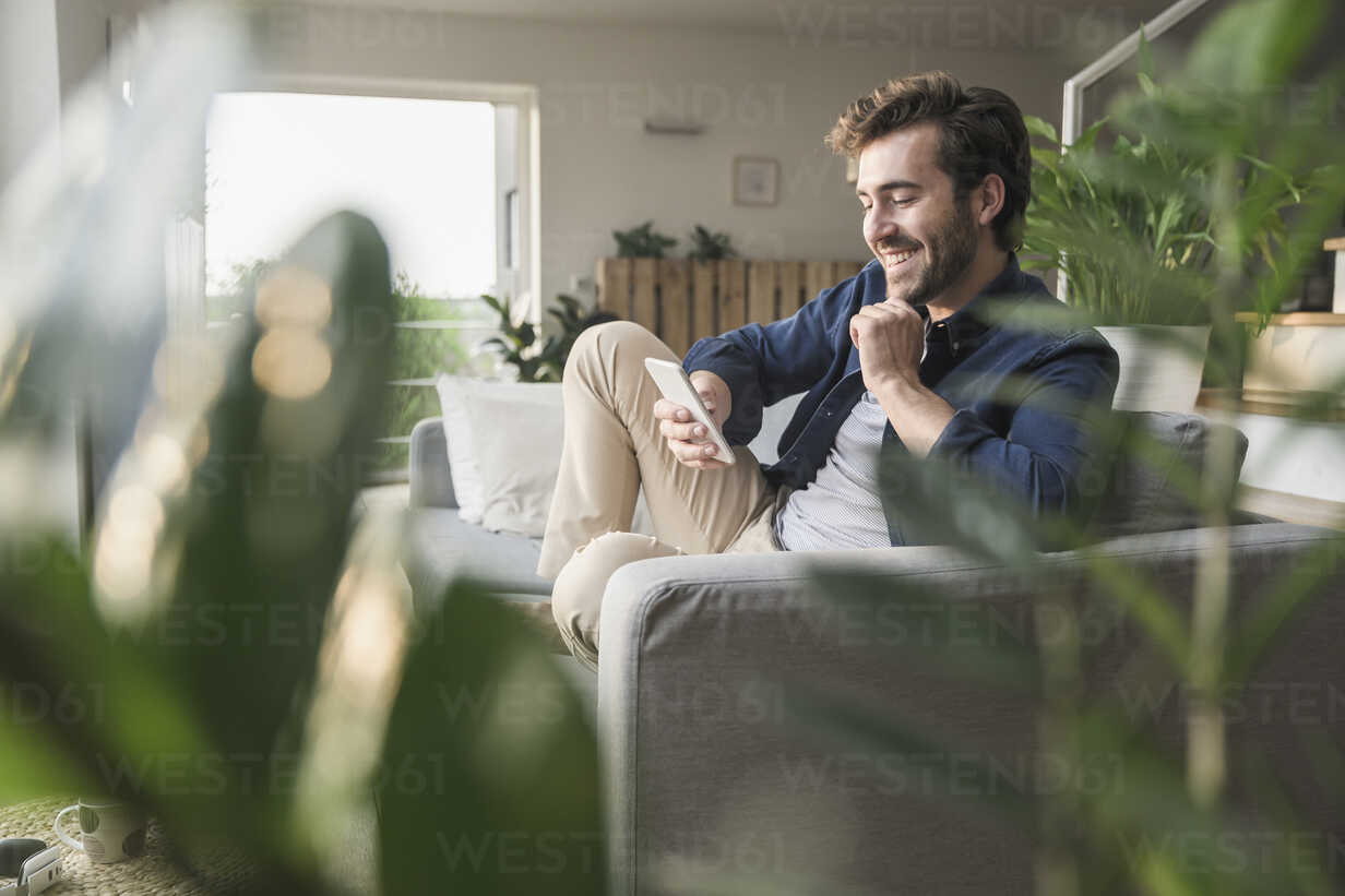 Young man sitting on couch at home, using smartphone - UUF17411 - Uwe Umstätter/Westend61