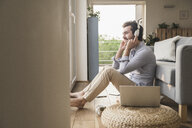Young man sitting at home on floor, using laptop, listening music - UUF17423