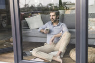 Young man sitting in front of window, drinking coffee - UUF17435