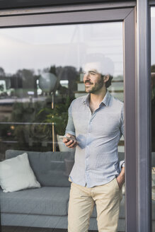 Young man looking out of window, using smartphone - UUF17438