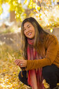 Smiling Asian woman holding leaf in autumn - BLEF02919