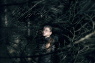 Caucasian teenage girl behind tree branches at night - BLEF02961