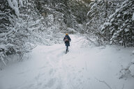 Caucasian woman hiking in snowy forest - BLEF02994