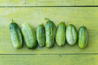 Green cucumbers in a row on wooden table - BLEF03036