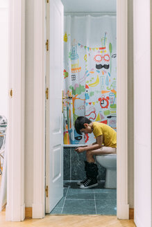 Boy playing video game on a games console, sitting on the loo - JCMF00050