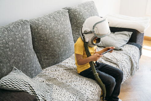 Kid lying on couch and playing with a video game console at home - JCMF00053