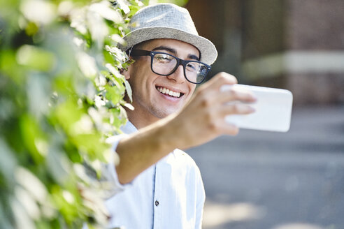 Portrait of young happy man taking selfie with hedge in background - BSZF01063