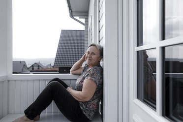 Portrait of smiling relaxed senior woman sitting on porch - KMKF00916