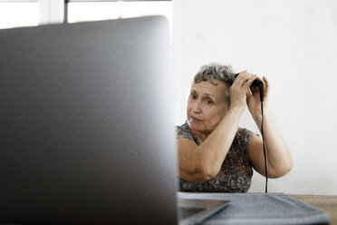 Senior woman sitting at table at home using laptop and doing her hair - KMKF00922