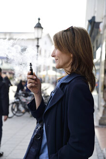 Mature woman smoking electronic cigarette in the city - ECPF00683